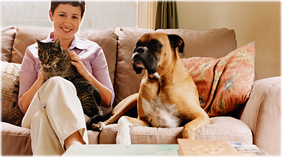 getty_rf_photo_of_woman_on_sofa_with_cat_and_dog.jpg